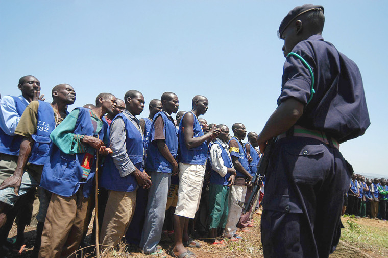 A policeman keeps an eye on former prisoners in Nteko, Rwanda, on Sunday. Some 774 Rwandans convicted by community courts began excavating stonesfor road construction as punishment for their role in the 1994 genocide of more than half a million people in this small central African nation.