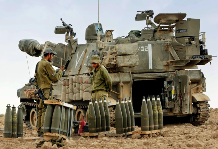 Israeli army gunners stand next to a mobile artillery piece and shells just outside the northern Gaza Strip Wednesday.
