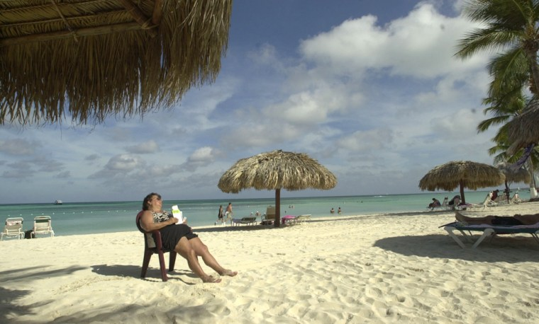 A tourist sleeps on Palm Beach on the northwestern coast of Aruba.