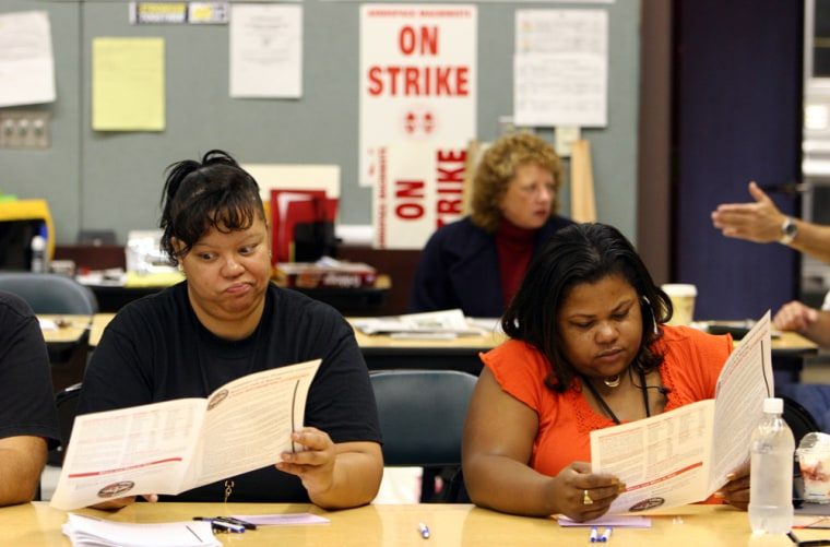 Union stewards Mary Seaton-Gaines, left, a factory service attendant, and Margie Purnell, production lead, read over the summary of the new proposed contract as the striking Boeing workers vote on the proposed contract in Seattle, Wash. on Thursday.