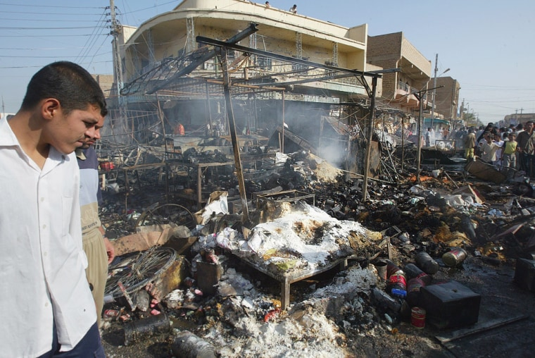 Local residents view destruction after suicide car bomber hits market in Iraqi town of Balad