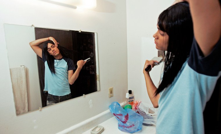 Alex Polanco adjusts his wig in his Menasha, Wis., apartment on Aug. 1, 2005. Polanco exists in a gray area, where gender is often blurred and where he feels no obligation to choose one gender over the other.
