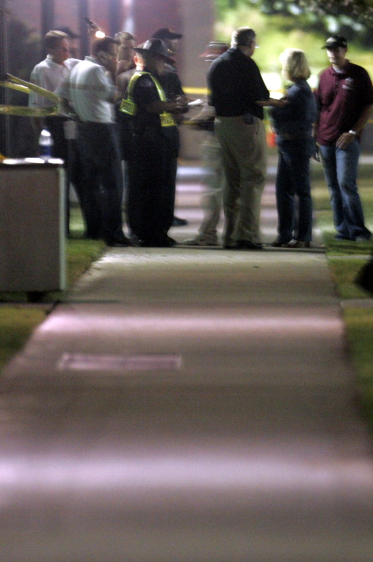Officials mill around inside the police perimeter after one person was killedby an explosionneara packed football stadium at the University of Oklahoma on Saturday.