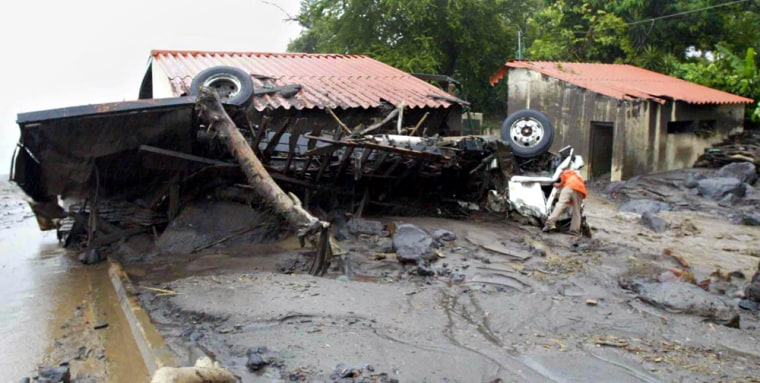 Remains of a truck lie on the side of a road in Planes de la Laguna, El Salvador, on Monday. A tropical weather front swept over Central America, unleashing downpours and causing rivers to overflow.