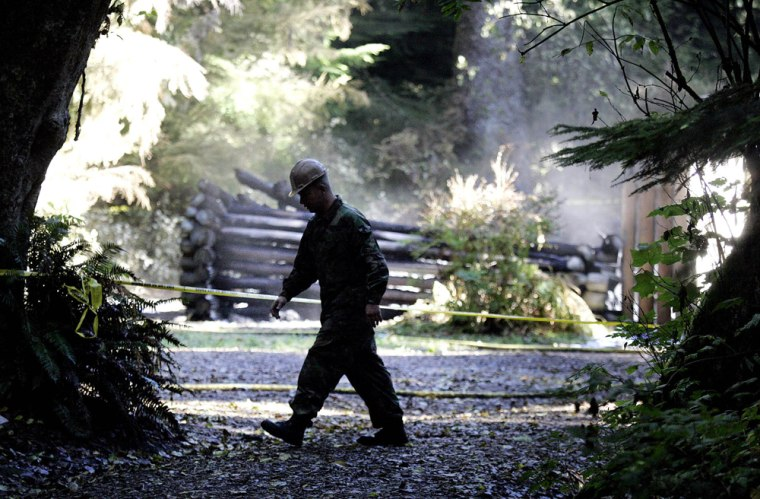 An official on Tuesday walks past the smoking ruins of a replica of thefort in Warrenton, Ore., where the Lewis and Clark expedition spent the winter of1805-1806.