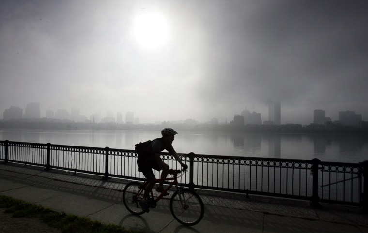 Cyclist rides along Charles River as the fog lifts from the Boston skyline in Cambridge