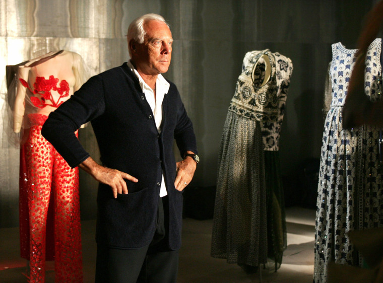 Italian designer Giorgio Armani stands next to his creations in Tokyo