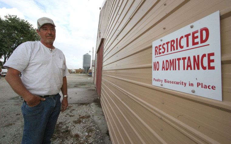 Poultry farmer David Conley stands next to a recently installed warning sign at his farm.