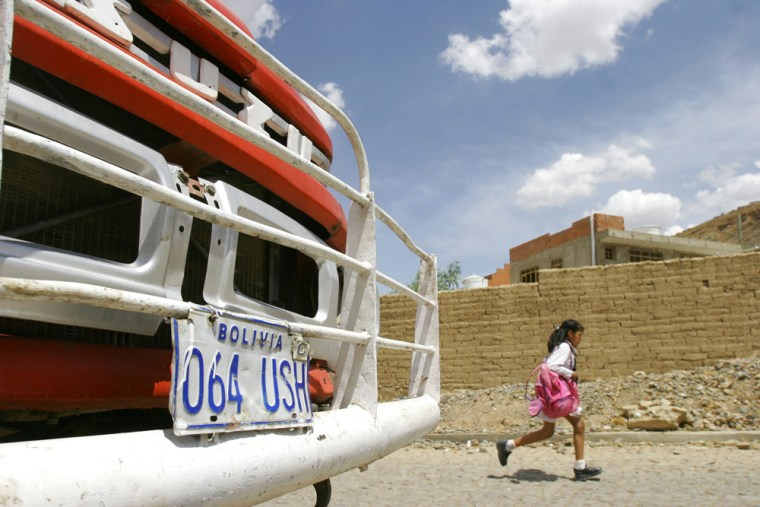 A Bolivian student runs past Monica Lozada's family's house in the city of Cochabamba, Bolivia, on Thursday. The woman's relatives are stunned by word of her killing, and are anxious to resolve a dispute over who should adopt Lozada's 4-year-old daughter.