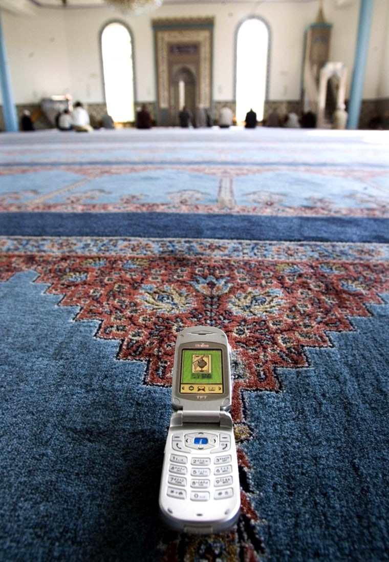 Thelightweight Ilkone i800 cellular telephone is seen in front of a group of people praying in a mosque inRotterdam. The Netherlands is the first European countrywhere the Islamic phone goes on sale.