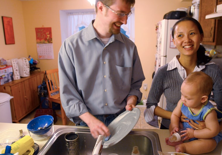 Mary Ngo, a Vietnamese immigrant, and her husband, Bernie Fischer, still do the dishes by hand and use the dishwasher as a drying rack. Son Gabriel watches the washing in their Columbia, Md., kitchen.