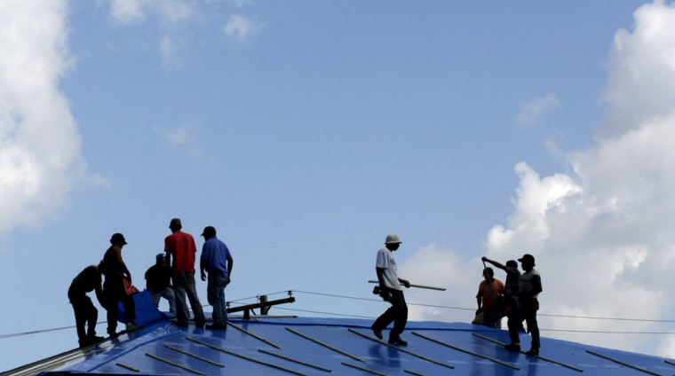 Construction workers with the Rabren General Contractors of Auburn, Ala., place a temporary plastic cover on a duplex home on Gadsen Street in Kenner, La., just outside New Orleans.