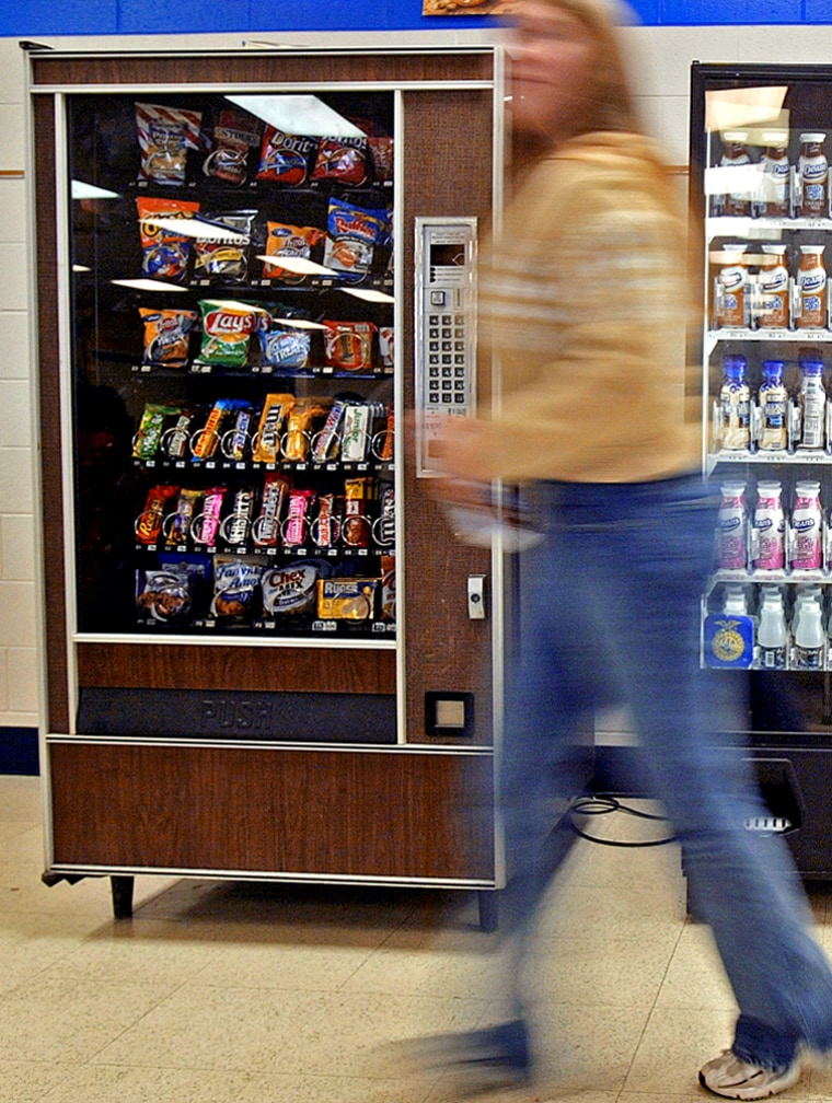 A student walks by a vending machine at Delavan-Darien High School in Delavan, Wis. For many Americans, the vending machine is as much a part of their daily diet as fast food restaurants.