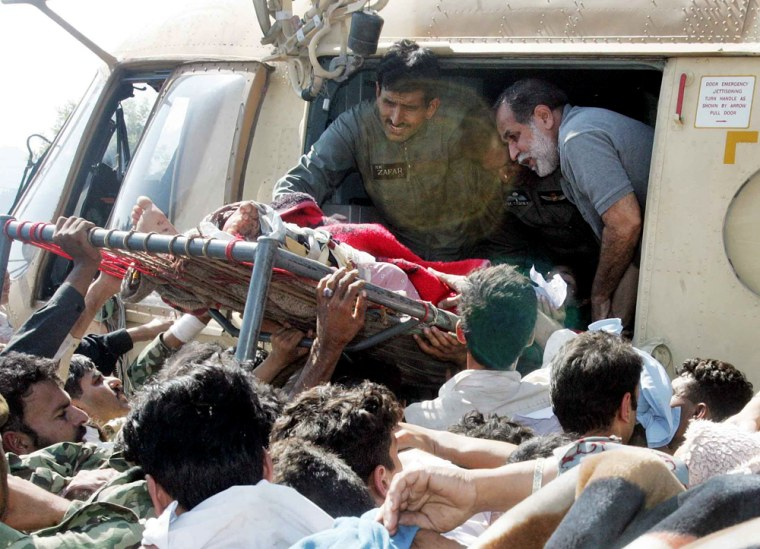 Earthquake victims are loaded onto a Pakistani army helicopter in Muzaffarabad