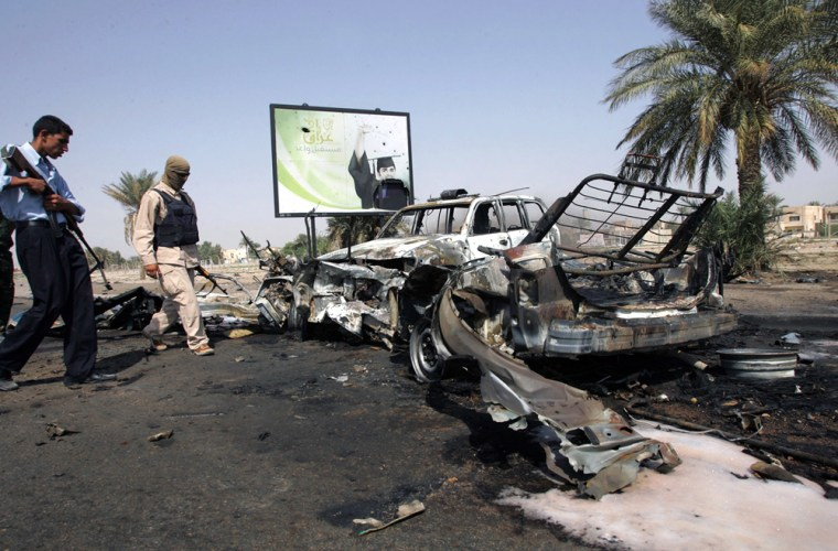 Iraqi policeman and soldier look at destroyed vehicles following attack on checkpoint in Baghdad