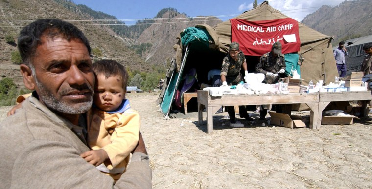 A Kashmiri man holds his child near a re