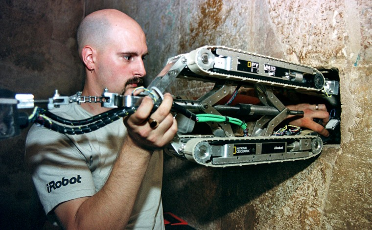 The shafts were last probed in September 2002. In this photo from that project, Gregg Landry, an engineer from the Boston firm iRobot, places a robot inside the shaft of the Great Pyramid in Cairo. The new robot has been designed by a university in Singapore.