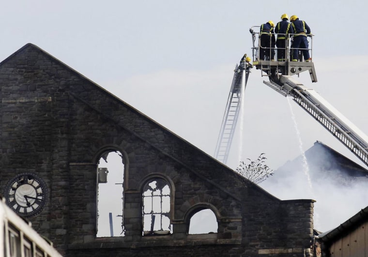Firemen douse hot spots from the fire that destroyed a warehouse belonging to Aardman Animations in Bristol, England, on Monday.