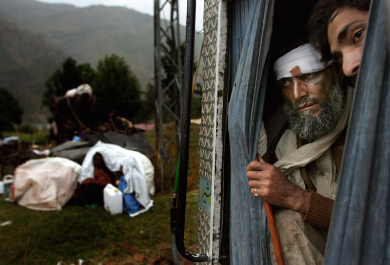 Pakistani earthquake survivors look out from the back of a truck as others take shelter from the rain near Balakot, Pakistan, onTuesday.