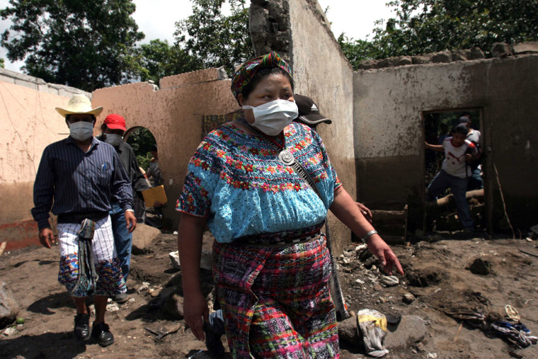 Nobel Peace Prize laureate Rigoberta Menchu walks through a mudslide in Panabaj, Guatemala, on Tuesday. President Oscar Berger, who accompanied Menchu on the inspection tour, said that more than 400 people had been killed by the mudslides in Panabaja alone.