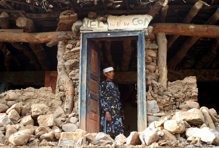 Indian survivor looks out from damaged house in Poonch