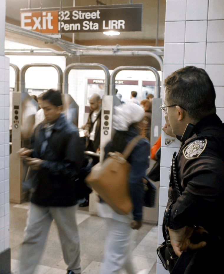 A New York City police officer observes people passing through Penn Station onTuesday. After four days on high alert, police announced Monday they were scaling back security measures in the subways because no evidence had emerged that an alleged terrorist plotwould be carried out.