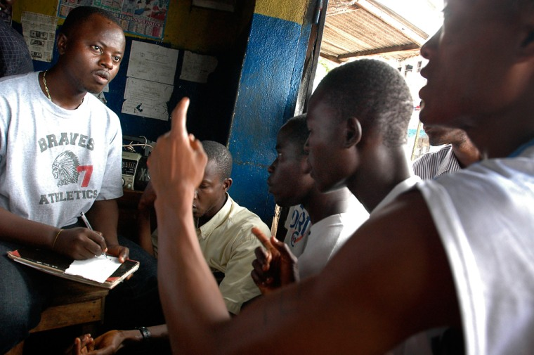 Liberian men react to election results over radio day after their presidential vote in Monrovia