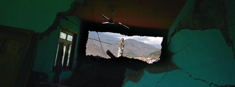 A man looks through a hole in an earthquake-destroyed home in Sanger, Pakistan, onWednesday. Across the region of northwest Pakistan destroyed by an earthquake, hundreds of villages remain cut off from help.