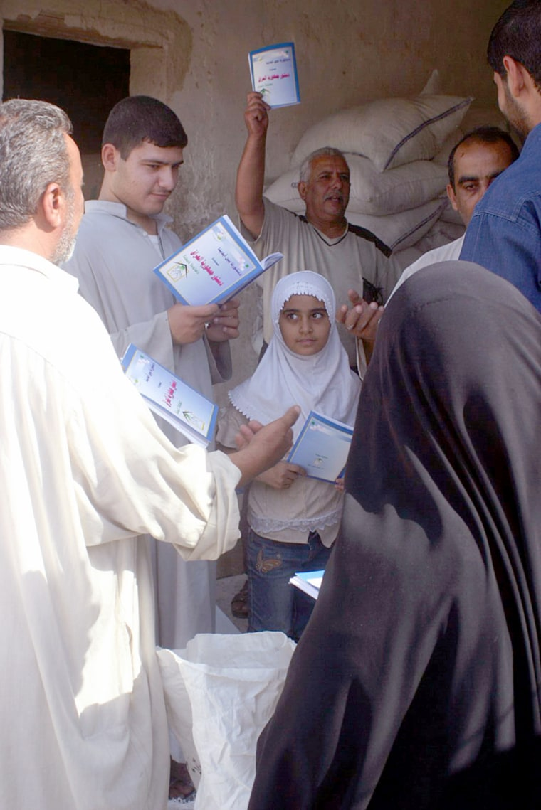 Iraqis receive copies of Iraq's new constitution during food rations distribution in Najaf