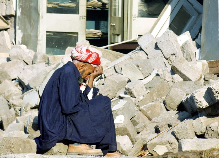 An earthquake victim sits in front of hi