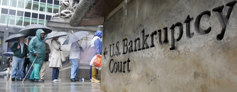 People wait in line under umbrellas against the rain outside U.S. Bankruptcy Court in New York onFriday. Thousands of consumers across the nation filed bankruptcy petitions Friday to beat the start of a new federal law that sets stricter standards for seeking protection from creditors.