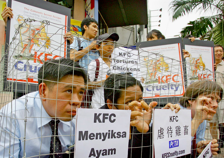 Members of People for the Ethical Treatment of Animals confine themselves to cage during protest outside Kentucky Fried Chicken outlet in Kuala Lumpur
