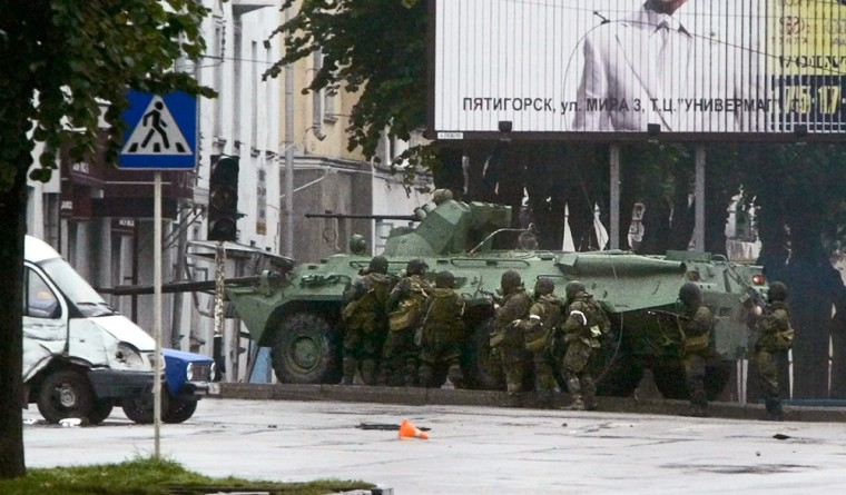 Russian special forces take cover behind an assault vehicleFriday as they approach a store in Nalchik where rebels had taken hostages.