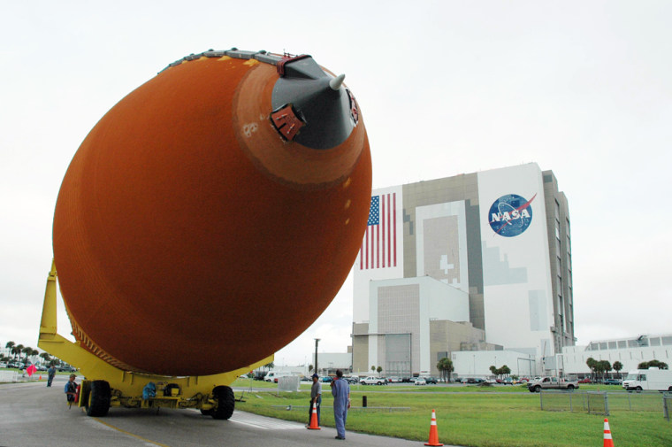 An external fuel tank for the space shuttle is transported around a turn, on its way from the Vehicle Assembly Building at NASA's Kennedy Space Center (in the background) to Turn Basin. The tank will take a barge trip from Kennedy Space Center to NASA's Michoud Assembly Facility in Louisiana for additional modifications.