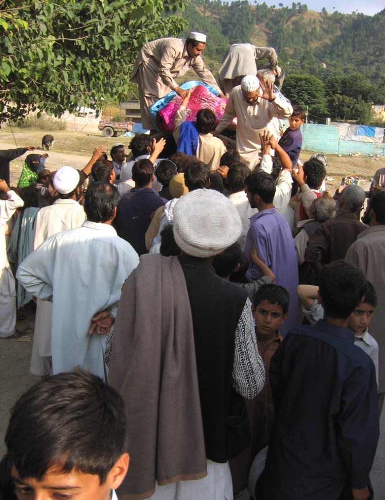 On the road to Muzzafarabad, Pakistan,a crowd gathers to collect tents and bedclothes passed out by volunteers.