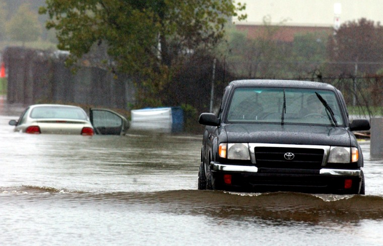 A truck makes a U-turn after attempting to cross a flooded area in Enfield, Conn., on Saturday.