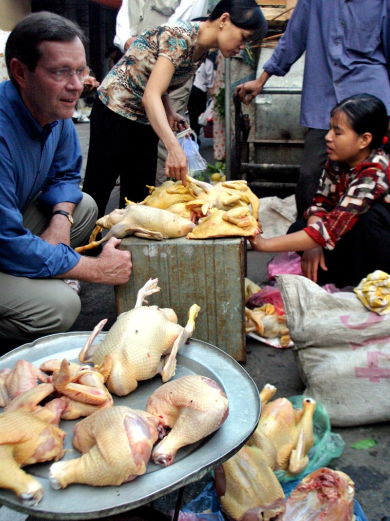US Health Secretary Leavitt sits next to slaughtered chickens on sale at Hang Be market in downtown Hanoi