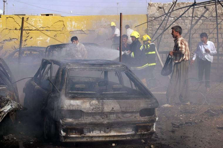 Iraqi firemen douse fire from a burning