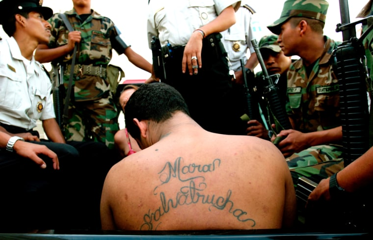 """A member of the Mara Salvatrucha gang is detained by army and police in Guatemala City onJuly 20. A string of violent killings targeting gang members and criminals in Guatemala has prompted rumors of a """"social cleansing."""""""