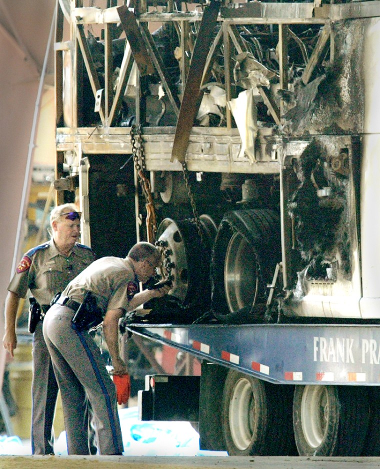 Texas highway patrol officers examine the back wheels of a bus that caught fire and exploded, killing 23 elderly Hurricane Rita evacuees, Sept. 23, 2005 in Wilmer, Texas.