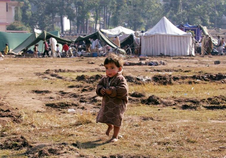A boy walks at a tent village in Muzaffarabad