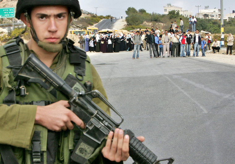 An Israeli soldier stands guard in front of Palestinians as they wait to be permitted to cross at El-Khader junction near Bethlehem