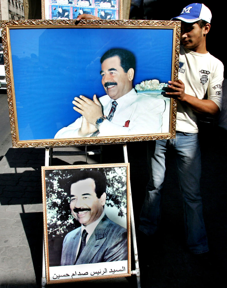 A Jordanian worker displays pictures offormer Iraqi leader Saddam Hussein for sale outside his shop in Amman, Jordan, onTuesday.