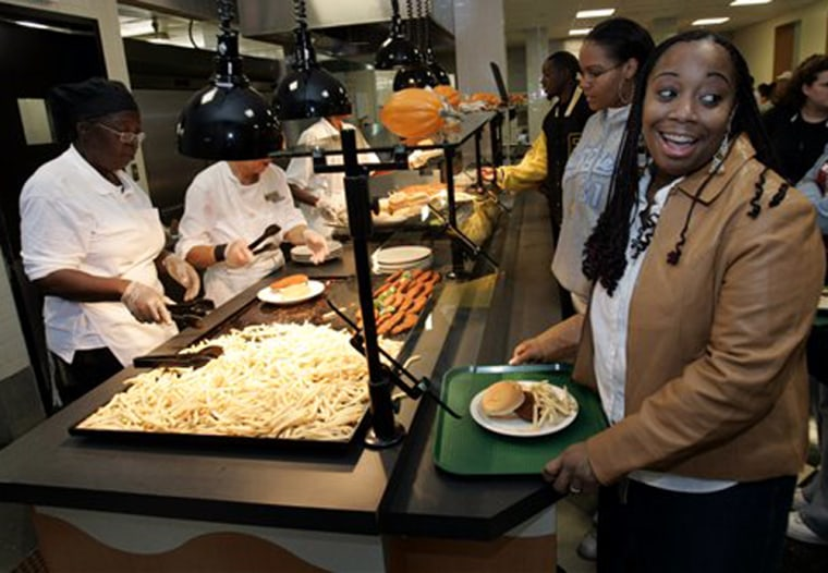 Norfolk State University student Tina Carroll, right, gets lunch in the school's cafeteriain thisOct. 13 file photo. At 187 pounds, well over what's recommended for her 5-foot-2 frame, she faces choices that could mean the difference between the body of her dreams or a lifetime of weight gain and disease.