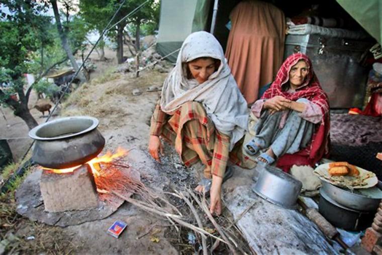 Baloor Jan, right, looks on as her daugher Zarifa Bejum, prepares water formorning tea in this Oct. 23 photo fromMunnasa, Pakistan.