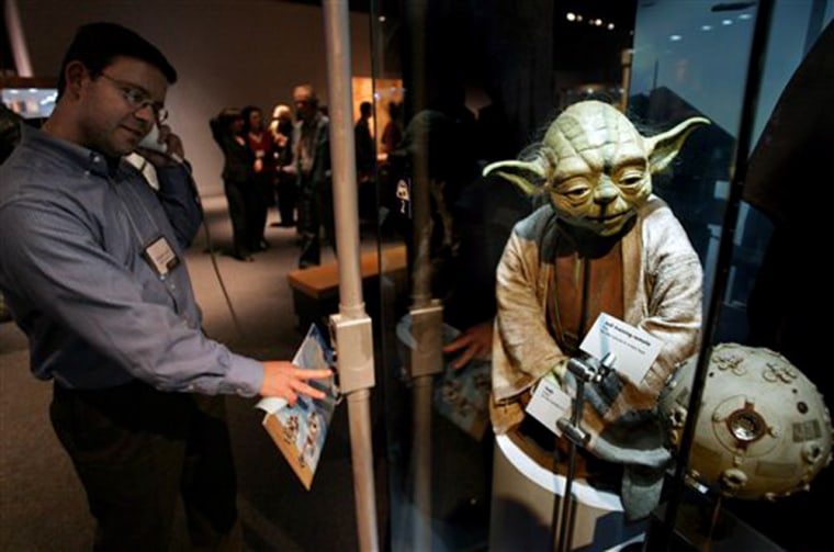"""Richard Greif, of Wakefield, Mass., listens to recorded information in front of a """"Yoda"""" puppet at the """"Star Wars: Where Science Meets Imagination"""" exhibit at the Museum of Science in Boston."""