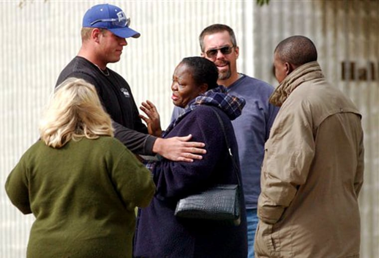 Oluwayinka Adeyooye, mother of missing 21-year-old Illinois State University student Olamide Adeyooye, center, is comforted by family, friends, and law enforcement personnel outside the Normal, Ill., police station in this Oct. 21 file photo.