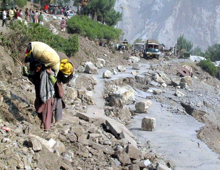Kashmiri earthquake survivors carry relief goods as they walk through a damaged road in Neelam Valley