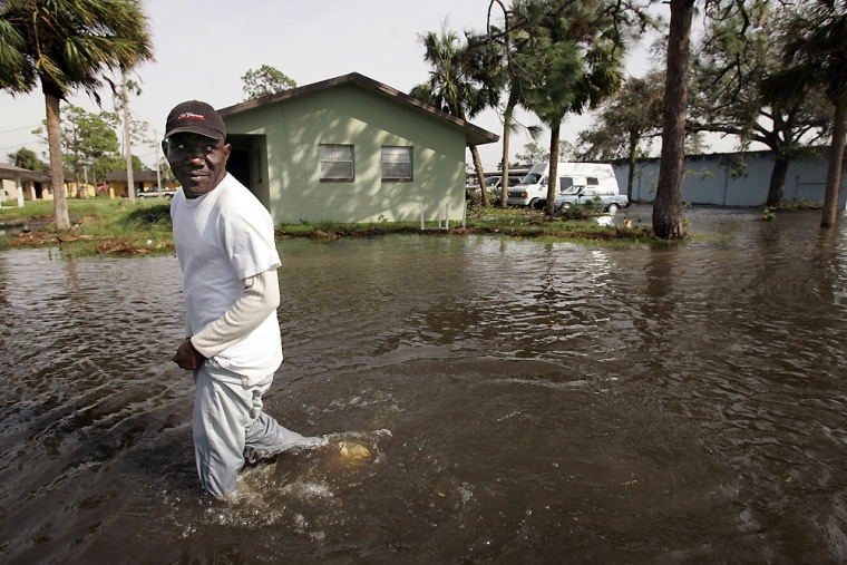Frantz Grache wades through the waters of his flooded labor housing compound in Immokalee, Fla. after Hurricane Wilma passed over. The hurricane knocked out some key crops in the state, and will mean higher costs for consumers.