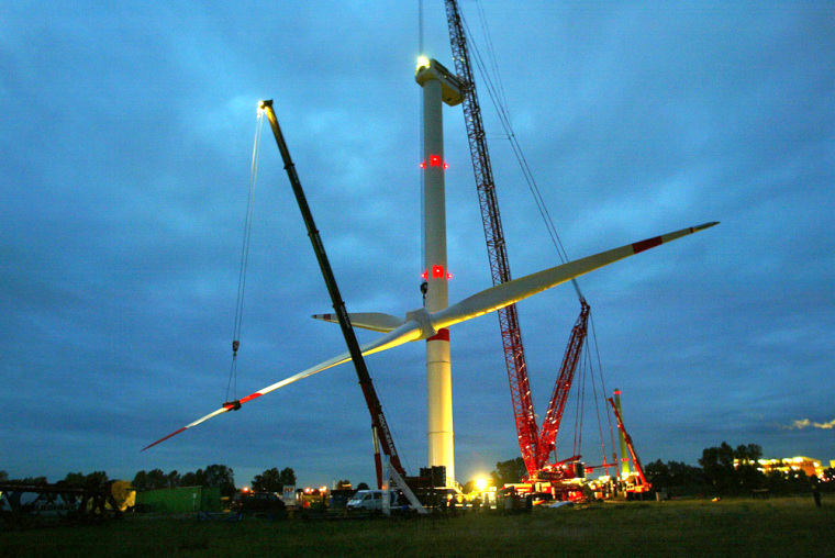 Cranes lift up the rotor of a giant wind generator near Hamburg